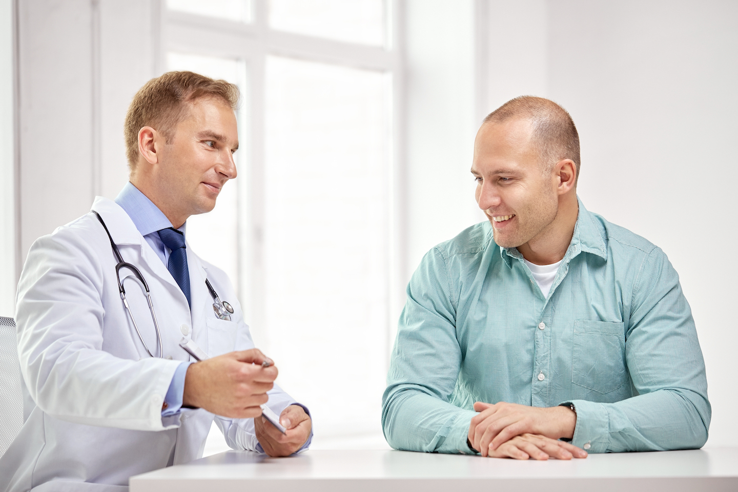 medicine, health care, people and prostate cancer concept – happy male doctor with clipboard and pat
